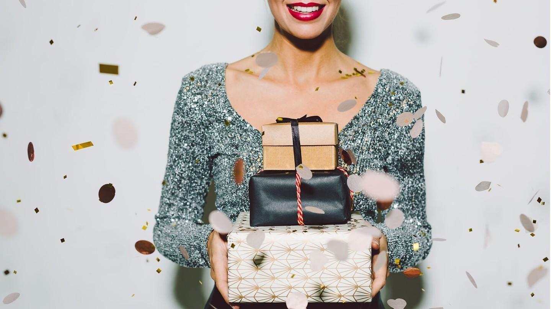 Schnell noch ein Geschenk: Frau hält Stapel mit Weihnachtspäckchen