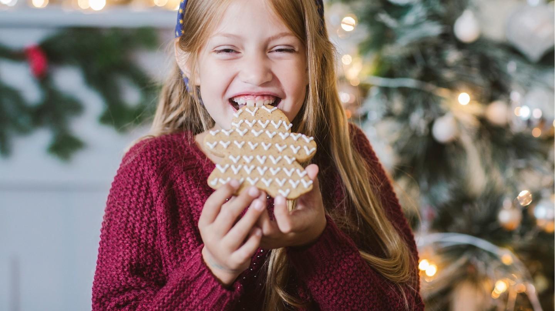 Ist Fluorid giftig oder wichtig für die Zähne? Ein Mädchen seht vor einem Weihnachtsbaum und beißt in einen großes Lebkuchen.