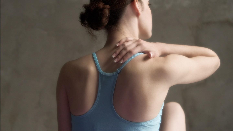 Hilfe bei Rückenschmerzen: Eine Frau im Muskelshirt massiert sich den Nacken- und Schulterbereich.