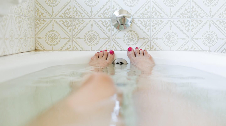 Tipps fürs Vollbad: Frauenfüße mit lackierten Nägeln schauen aus einer Badewanne heraus.