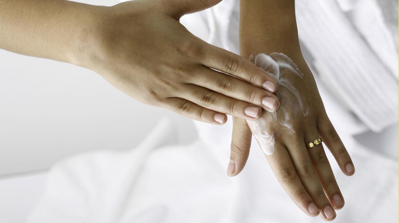 Trockene Hände: Eine Hand cremt die andere ein.