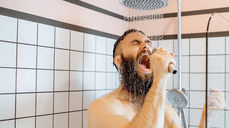 Den Vagusnerv aktivieren: Junger Mann mit Bart singt unter der Dusche.