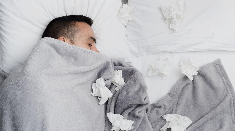 Grippe: Mann liegt im Bett, die Decke halb über den Kopf gezogen, um ihn herum liegen zerknüllte Taschentücher.