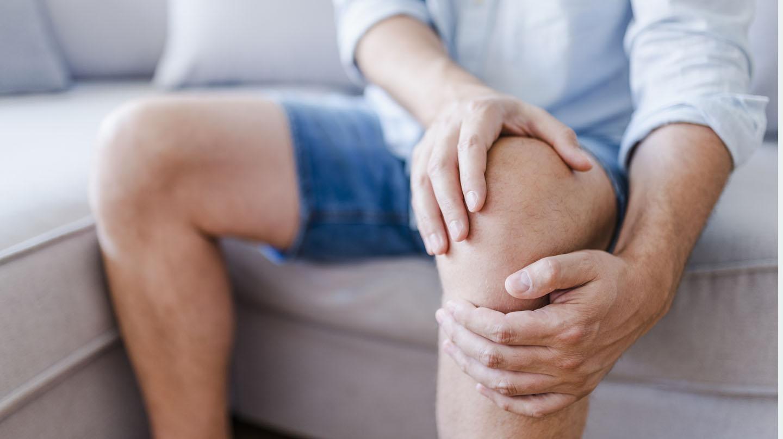 Gelenkschmerzen: Mann mit Shorts sitzt auf Sofa und umfasst ein Knie mit den Händen.