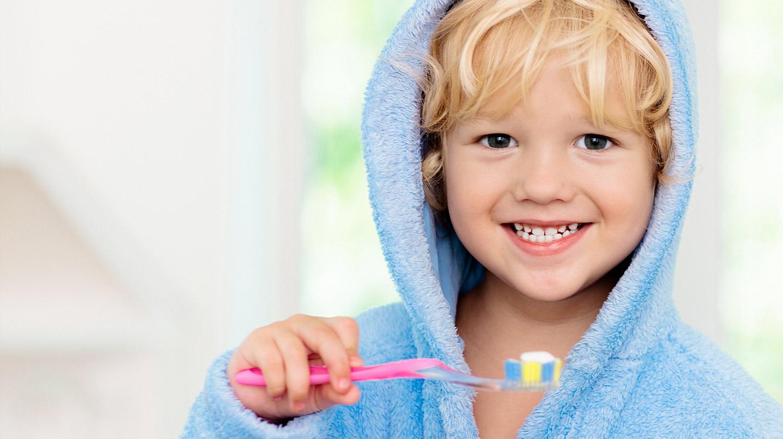 Kreidezähne: Kleiner Junge in hellblauem Bademantel hält Zahnbürste in der Hand.