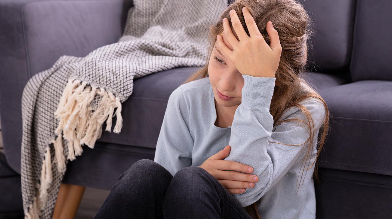 Ständig Kopfschmerzen bei Kindern: Mädchen fasst sich mit der Hand an den Kopf.