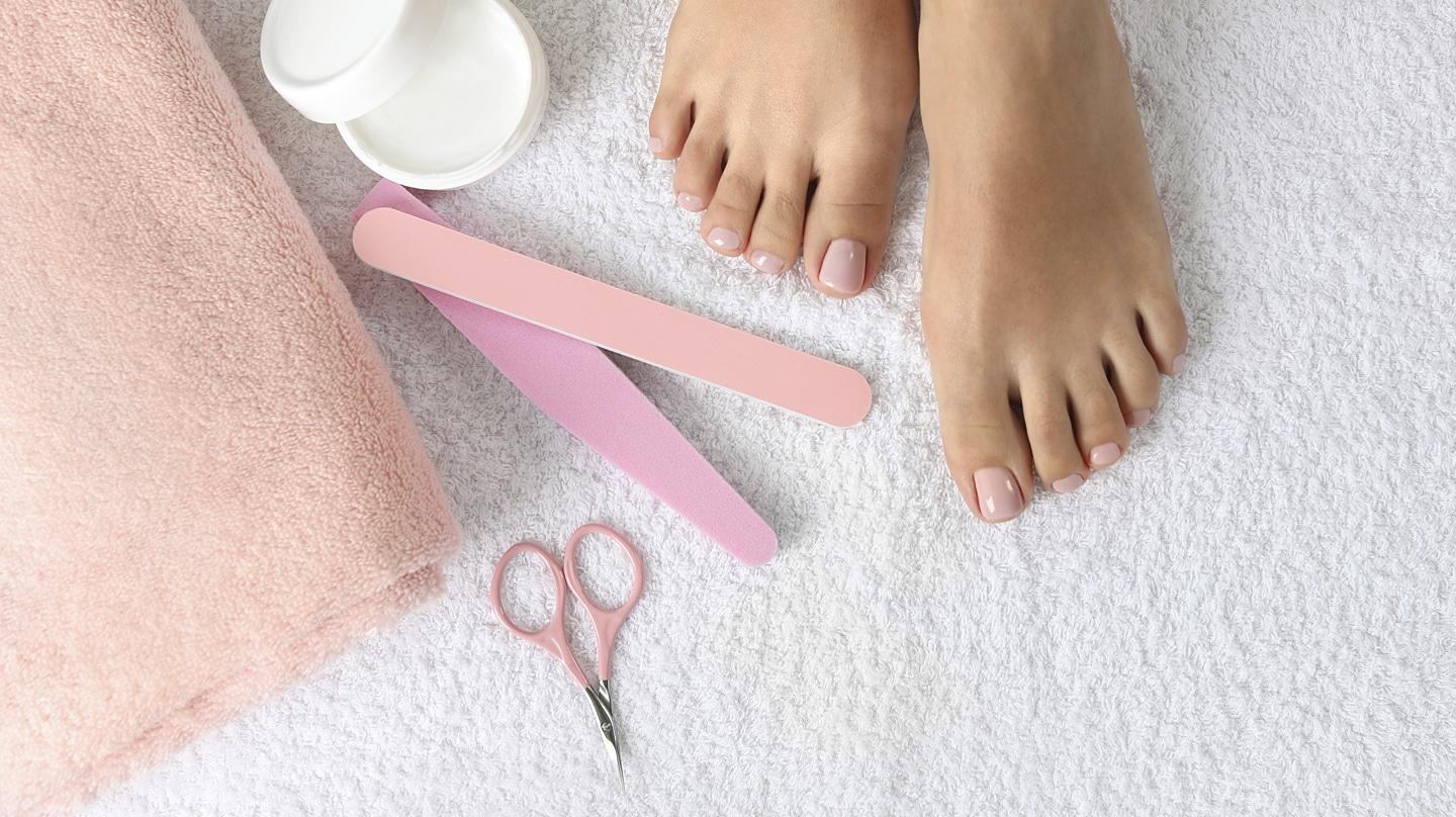 Nagelpilz behandeln: Gepflegte Füße mit roséfarben lackierten Nägeln. Daneben rosafarbene Nagelschere, Nagelfeile, Polierer, Handtuch und ein geöffnetes Cremedöschen.